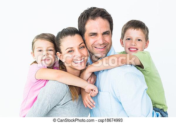 Fröhliche junge Familie, die zusammen Kamera sieht - csp18674993