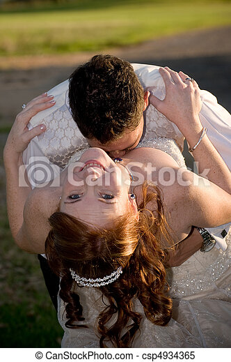 just married couple with groom kissing bride in the cleavage on a sunny day - csp4934365