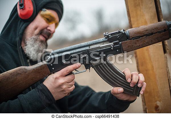 Kalashnikov riffle cartridge bullet clip reloading. Load and unload ak47 - csp66491438