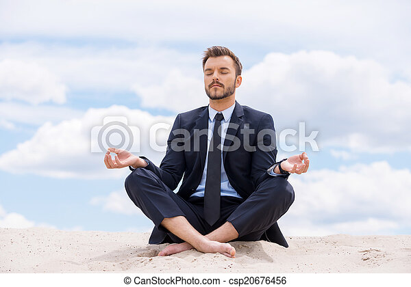 Keeping calm inside his soul. Handsome young businessman meditating while sitting in lotus position on sand and against blue sky - csp20676456