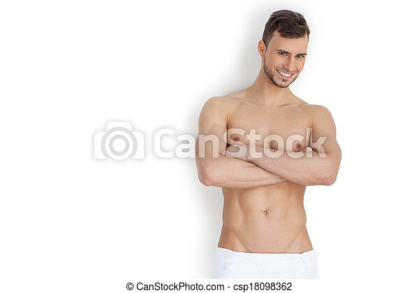 b26192093 Keeping his body in good shape. Cheerful young muscular man looking at  camera and keeping