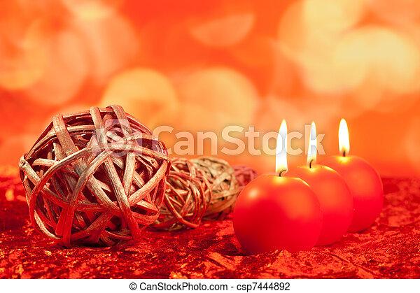 Weihnachtskerzen mit getrockneten Baubeln auf Rot - csp7444892