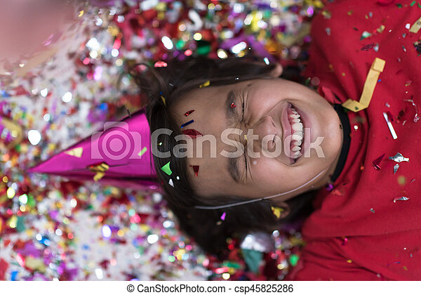 kid blowing confetti while lying on the floor - csp45825286