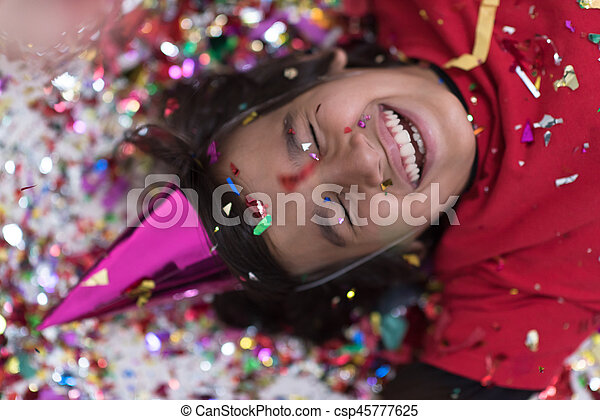 kid blowing confetti while lying on the floor - csp45777625