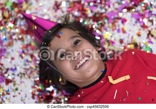 kid blowing confetti while lying on the floor - csp45632506