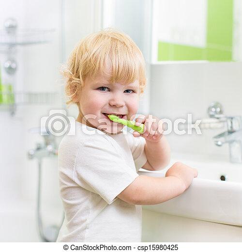 Kid boy brushing teeth in bathroom - csp15980425