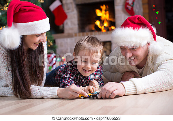 Kid boy playing toy cars with his parents under the christmas tree - csp41665523