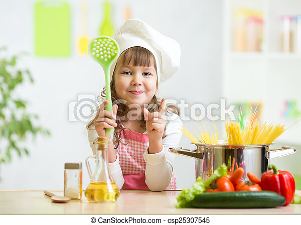 Kid cook makes healthy vegetables meal in the kitchen - csp25307545