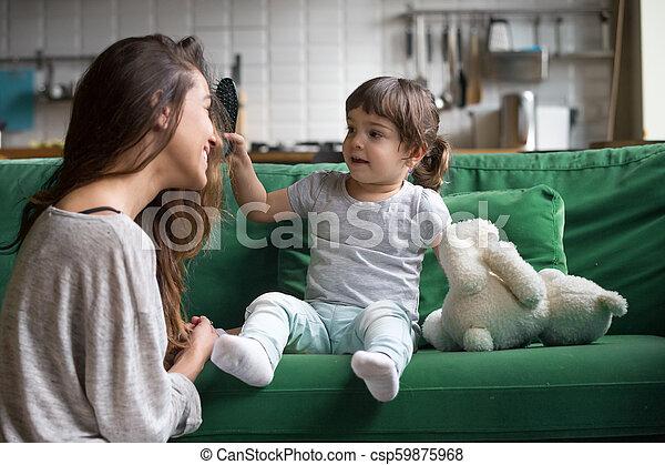Kid Girl Brushing Mothers Hair Having Fun Playing At Home Cute Kid