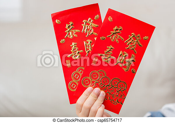 kid holding pair of red pockets written KUNG HEI FAT CHOY translation-wshing you prosperity - csp65754717
