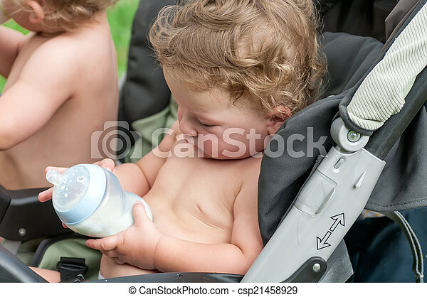 kid looks at the bottle of porridge sitting in a wheelchair - csp21458929