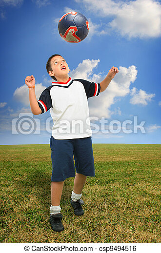 Kid playing soccer outside - csp9494516