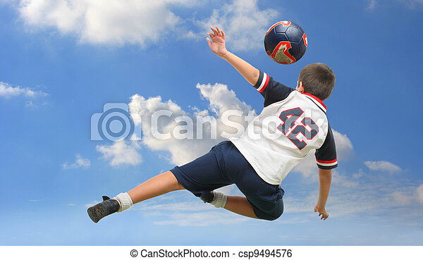 Kid playing soccer outside - csp9494576