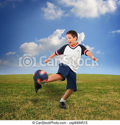 Kid playing soccer outside - csp9494515
