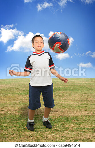 Kid playing soccer outside - csp9494514