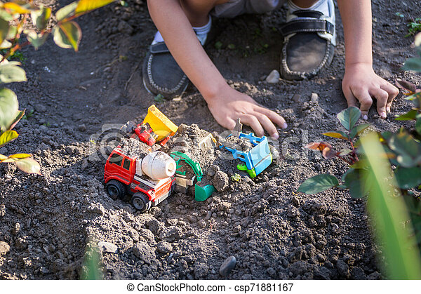 Kid playing with Plastic Toy Tractors in yard - csp71881167
