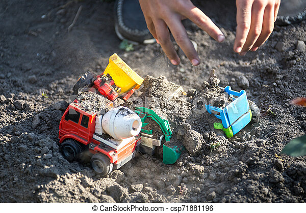 Kid playing with Plastic Toy Tractors in yard - csp71881196