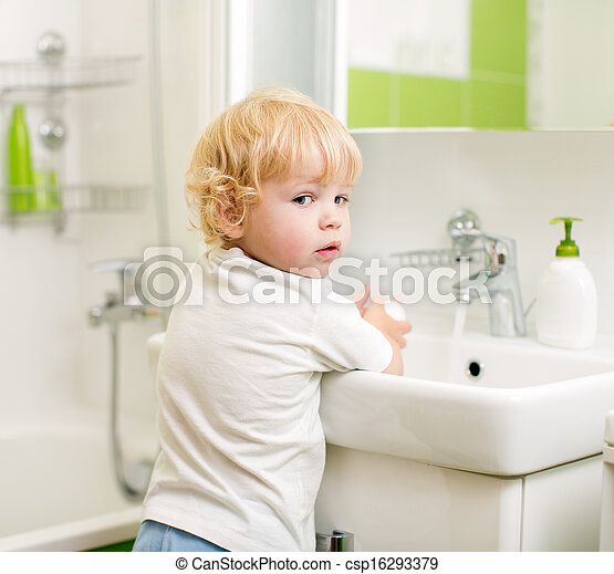 kid washing hands with soap in bathroom - csp16293379