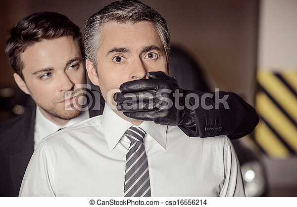 Kidnapping. Aggressive young men covering businessman mouth with his hand in glove - csp16556214