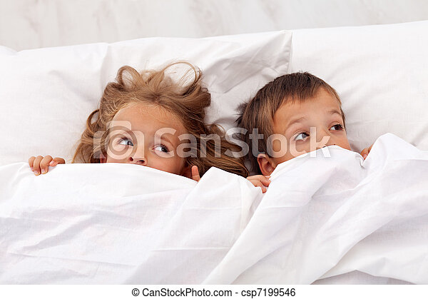 Kids afraid pulling the quilt on their heads - csp7199546