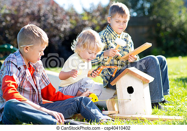 Cool Kids Boys Play And Build Birdhouse Sitting On Green Grass Download Free Architecture Designs Scobabritishbridgeorg