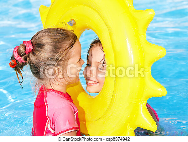 Kids on inflatable ring in swimming pool. - csp8374942