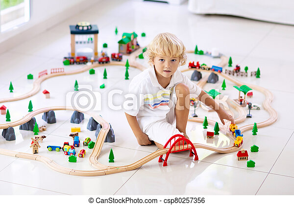 Kids play wooden railway. Child with toy train. - csp80257356