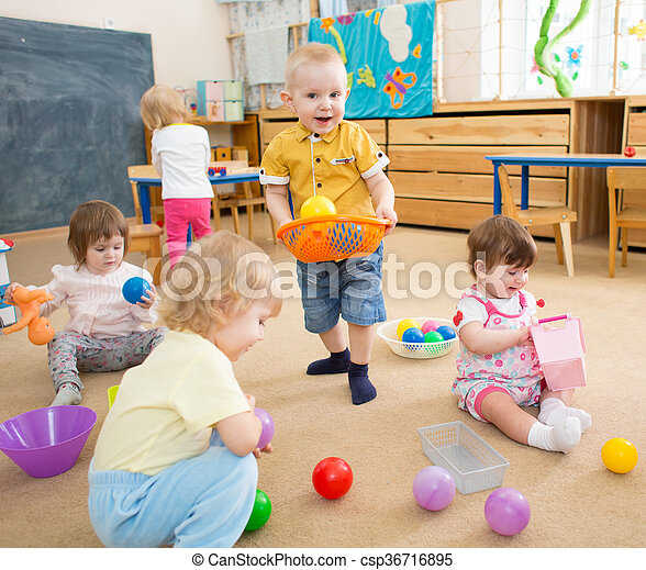 kids playing with balls in kindergarten room  - csp36716895