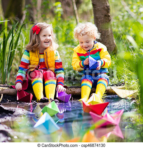 Kids playing with colorful paper boats in a park. Children play ...