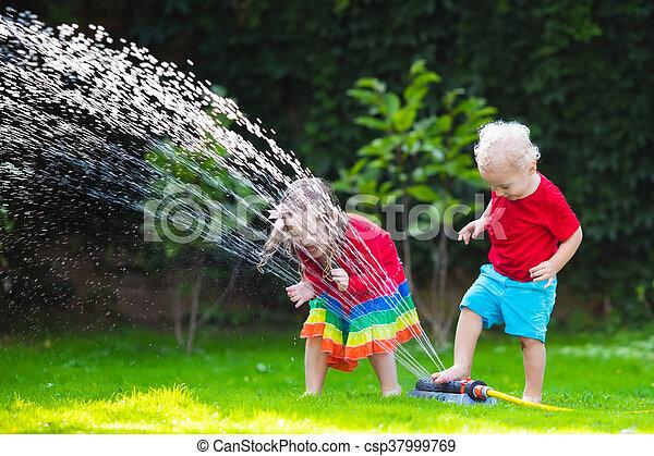 Kids playing with garden sprinkler - csp37999769
