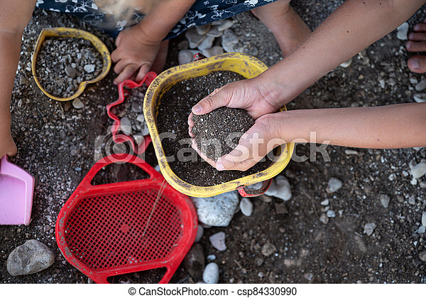 Kids playing with sand and dirt  and plastic toys - csp84330990
