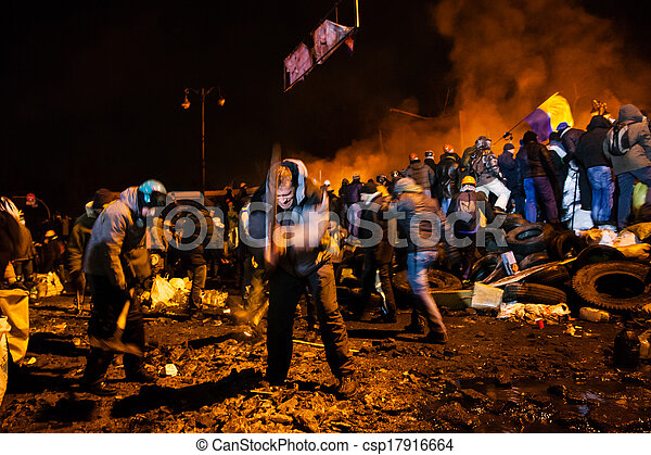 KIEV, UKRAINE - January 24, 2014: Mass anti-government protests in the center of the Ukrainian capital Kiev. Popular Resistance Warrior preparing to storm by government troops on Hrushevskoho St. - csp17916664