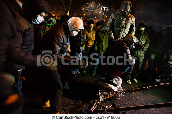 KIEV, UKRAINE - January 24, 2014: Mass anti-government protests in the center of the Ukrainian capital Kiev. Popular Resistance Warrior preparing to storm by government troops   on Hrushevskoho St.  - csp17916665