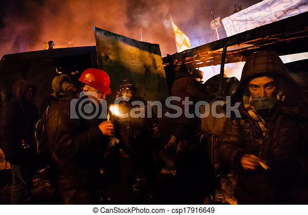 KIEV, UKRAINE - January 24, 2014: Mass anti-government protests in the center of the Ukrainian capital Kiev. Popular Resistance Warrior preparing to storm by government troops  on Hrushevskoho St.   - csp17916649