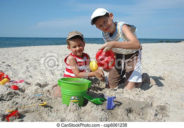 Kinder spielen mit spielzeug am strand. Zwei junge jungs
