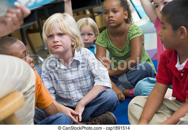 Kindergarten children listening to a story - csp1891514