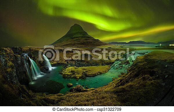 Aurora en Kirkjufell y cascada Kirkjufellsfosss, punto de referencia de Islandia. - csp31322709