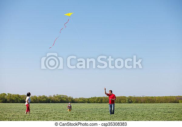 Familia corriendo con una cometa. - csp35308383