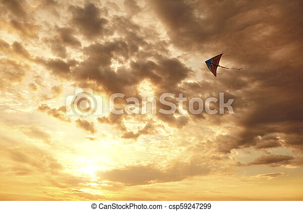 Kite flying in the sky with clouds at sunset - csp59247299