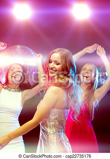 Drei lächelnde Frauen tanzen im Club - csp22735176