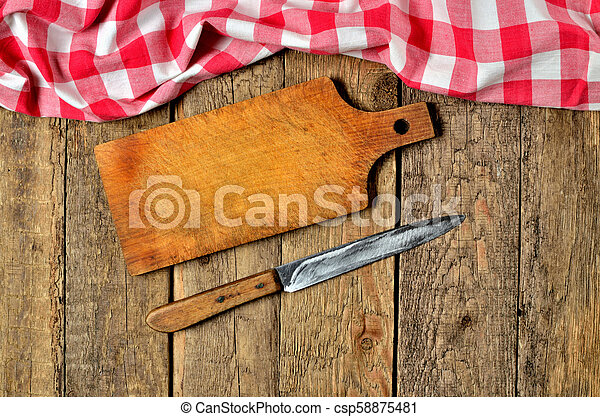 Knife next to wooden cutting board and a red checkered tablecloth top frame on wooden table background - csp58875481