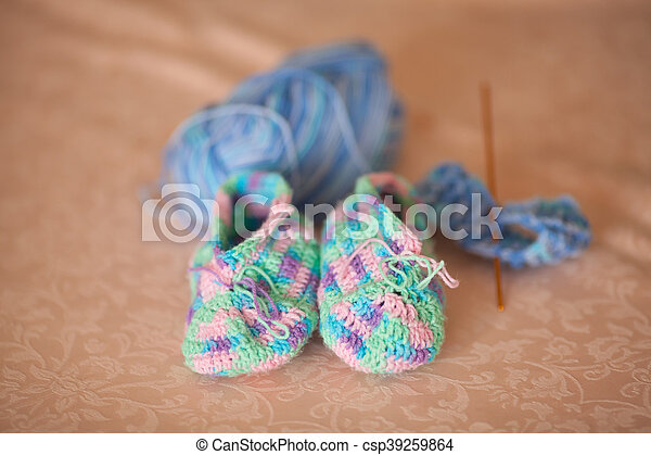 Knitted baby booties on a sofa, hand made - csp39259864