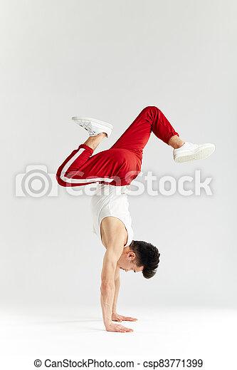 Korean dancer executes basic freezes of downrock brea dance isolated on white - csp83771399