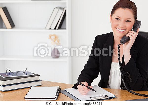kvinde, kontor, red-haired, siddende, notepad, telefoner., skrift, mens, kønne, tøjsæt - csp6486941
