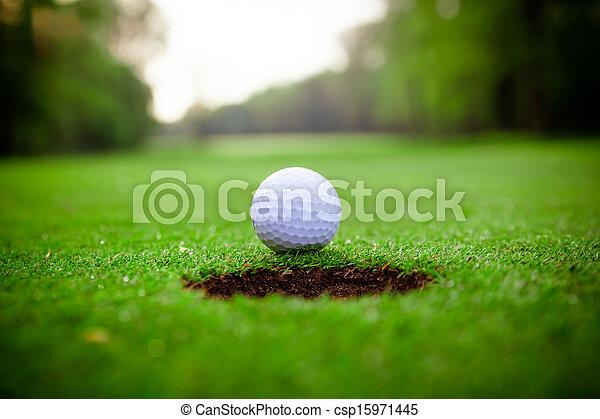 Bola de golf en labio de taza - csp15971445