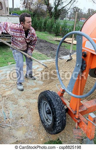 Laborer shoveling sand - csp8825198
