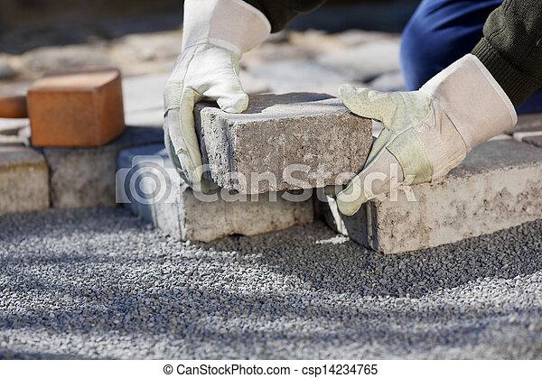 Trabajador de construcción pavimentando el camino de ladrillos - csp14234765