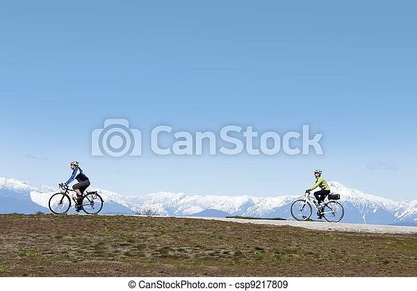 Lady on the bike with mountains - csp9217809