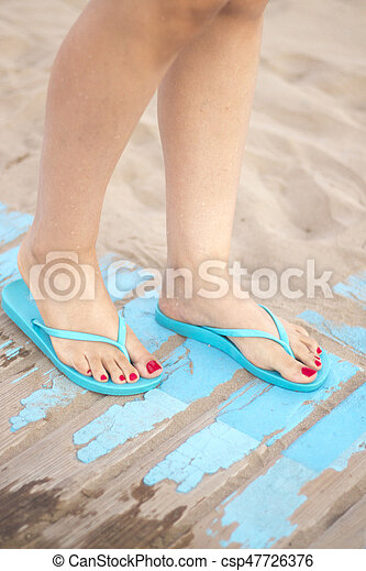 Lady's feet in sandals on beach - csp47726376