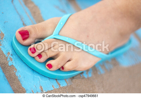 Lady's feet in sandals on beach - csp47949661